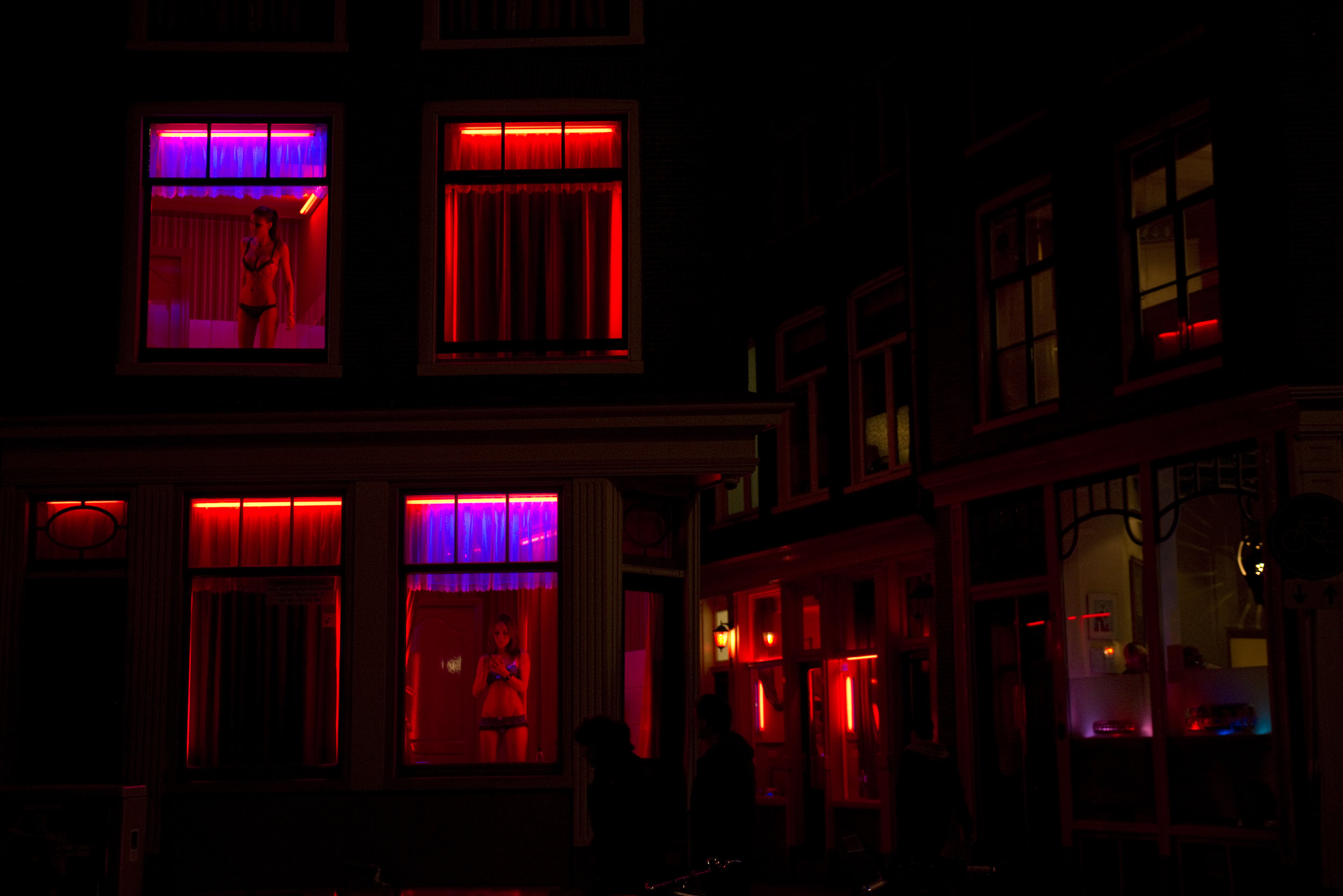 Two workers renting out rooms in Amsterdam's Red Light District,  De Wallen , wait for customers during the night. Prostitution is legal and strictly regulated in the Netherlands.