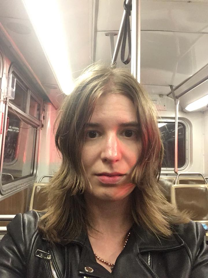 """I do an ongoing photo series called """"Empty-Bus Selfies"""" and on August 19, 2018, I got to take one on my way to Nopa. """"10-Year SF-Versary Resting Sad Face // contemplating my past and future, a deer caught in the glow of passing ambulance lights"""" I captioned it on Facebook. It's not a flattering picture, yet I'm proud of how well it captures my mood on that night."""