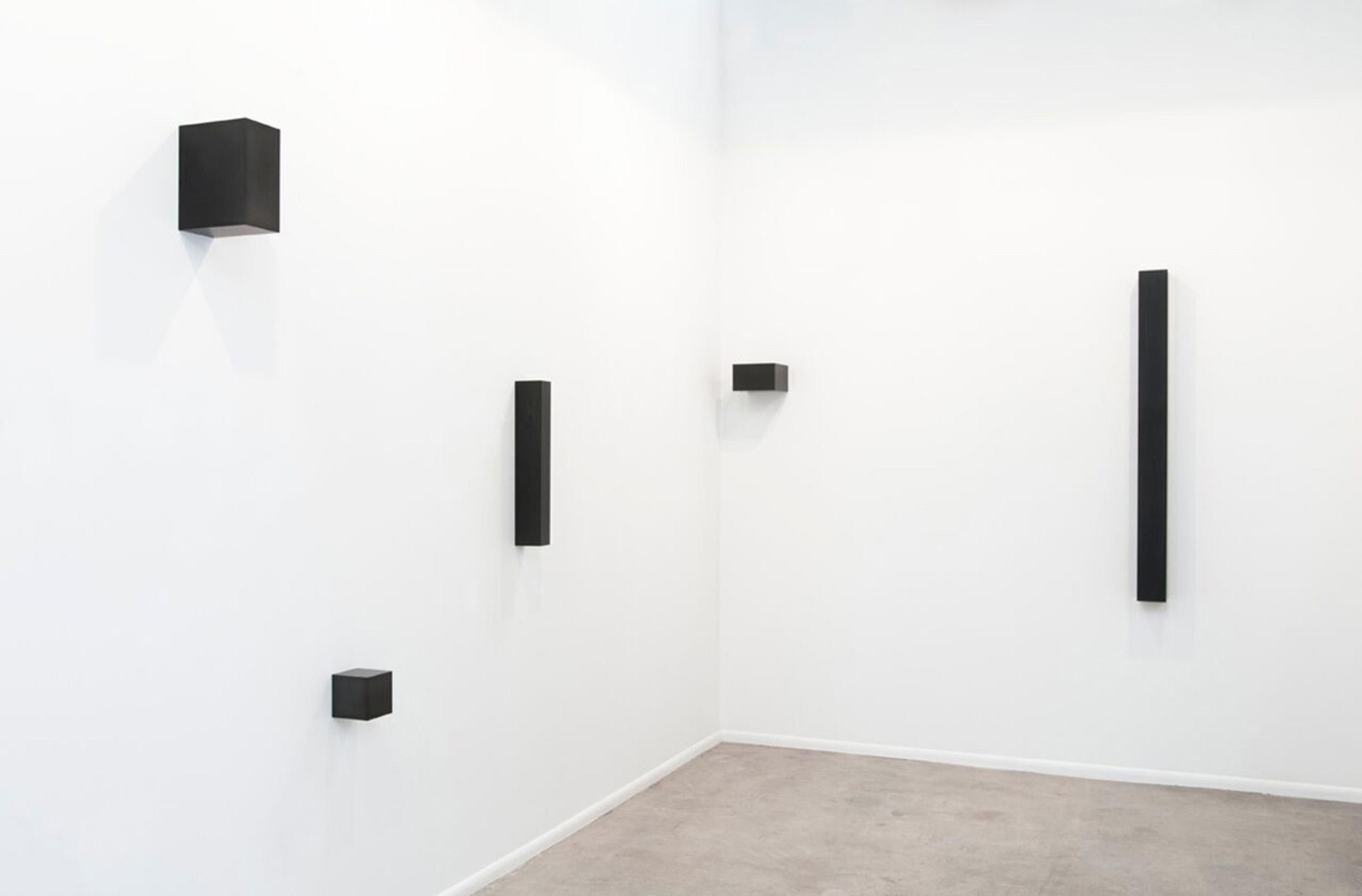 "Graphite Sculptures (l to r), Askew Cube, 2011, 7.5"" x 7.6"" x 7.6""; Cube, 2015, 5.1"" x 5.1"" x 5.1""; Vertical Bar, 2009, 24.25"" x 3.25"" x 4.25"";  Golden Mean Horizontal, 2015, 5.4"" x 8.9"" x 8.9""; Untitled (Column), 2015, 3"" x 3"" x 70"""