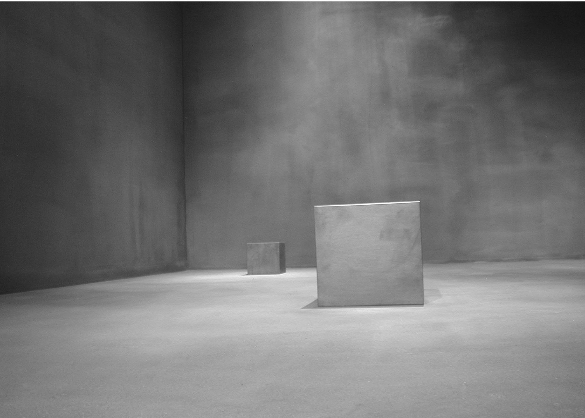 """Center of Gravity (installation detail view, School of the Art Institute of Chicago, 2004)   Rectilinear Solid (foreground), 2004, Solid graphite,18"""" x 12"""" x 12""""  Panza Collection"""
