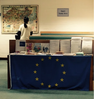 A table with several books on top and the EU flag  draped over the edge. A person is in the background looking at a map.