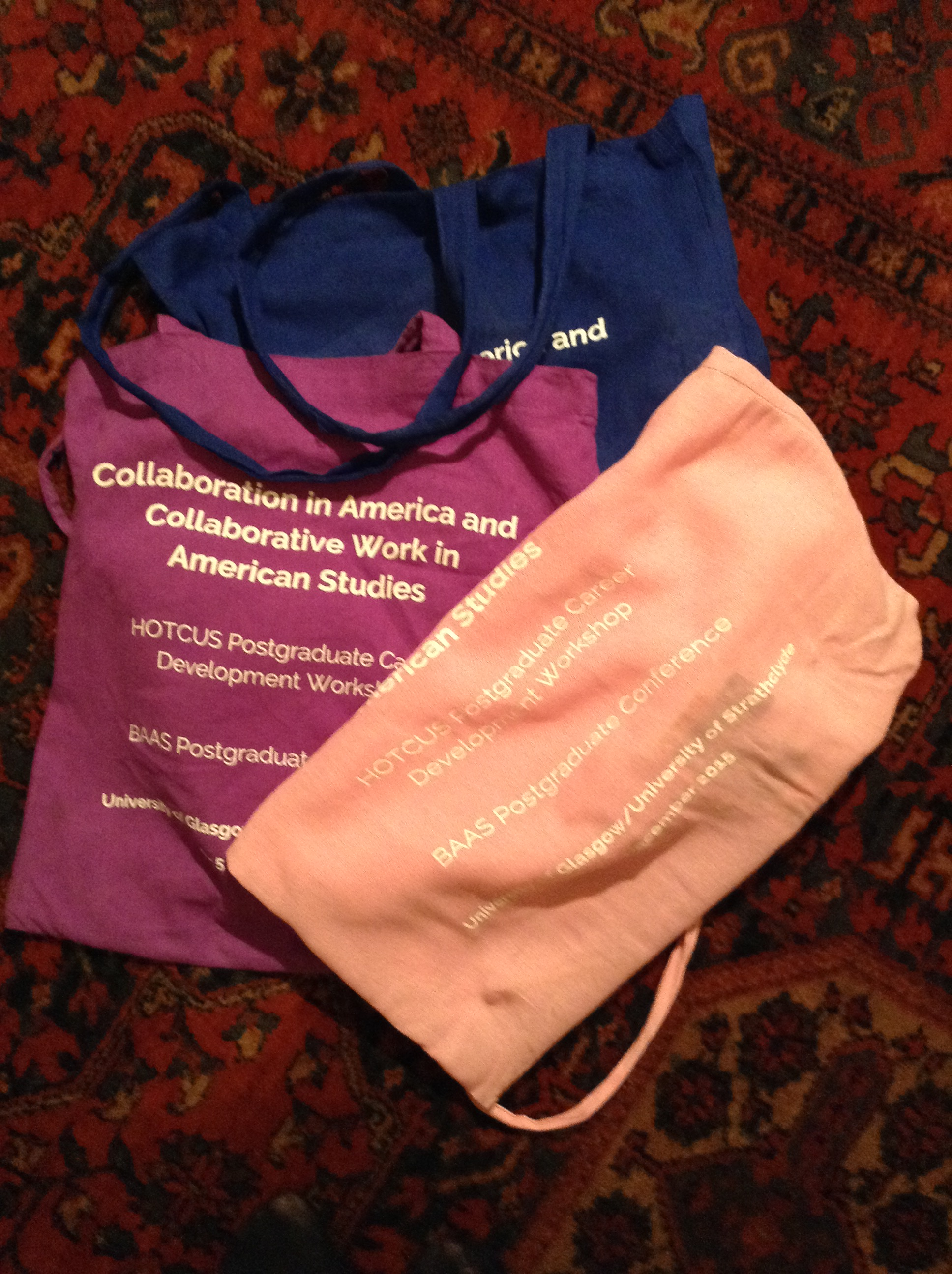 Three conference tote bags in navy, purple and peach. Conference details are printed on the badges.