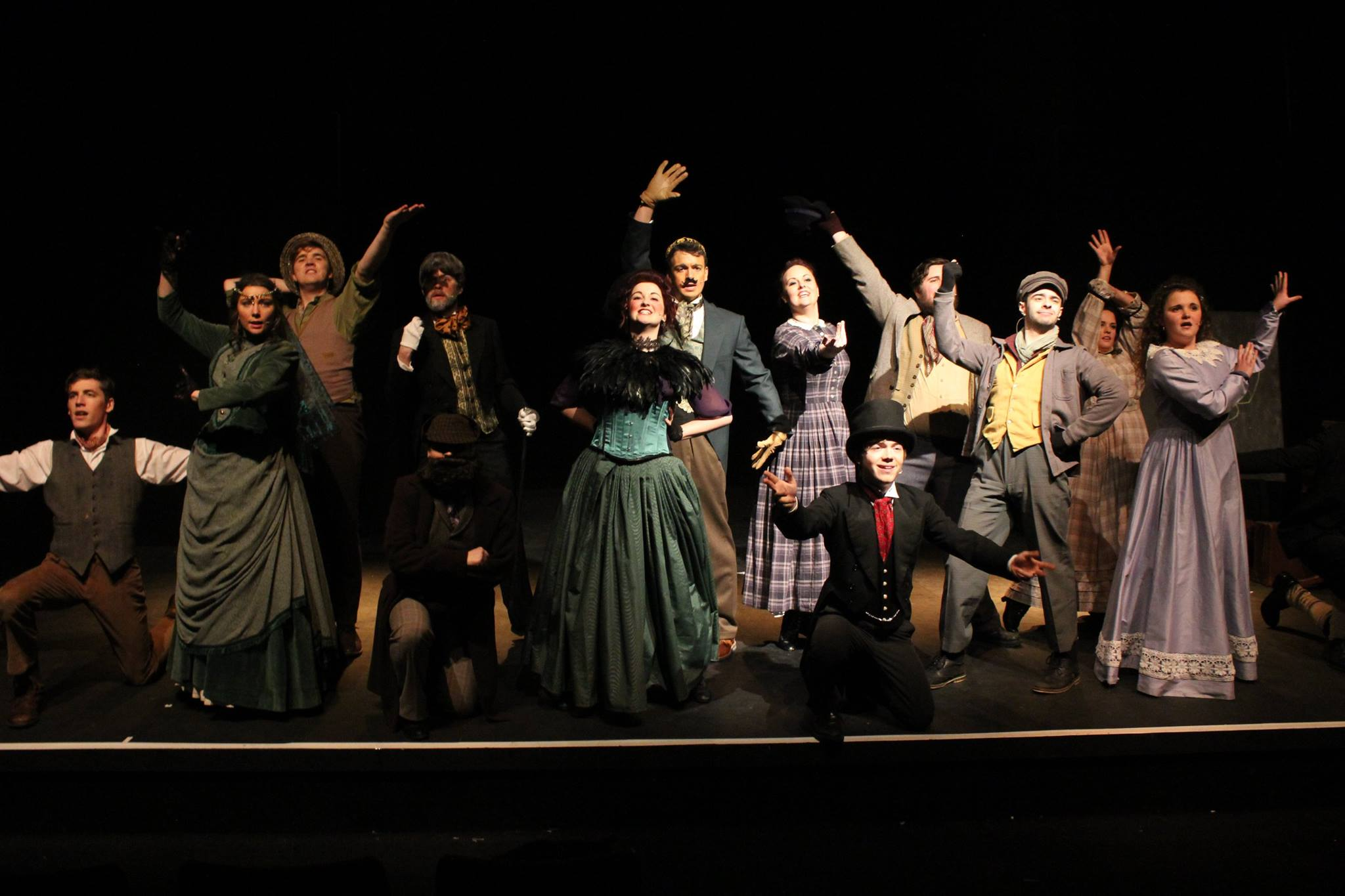 The finale scene from the Mad Props Theatre production of A Mystery of Edwin Drood. All of the cast are on stage with arms in the air
