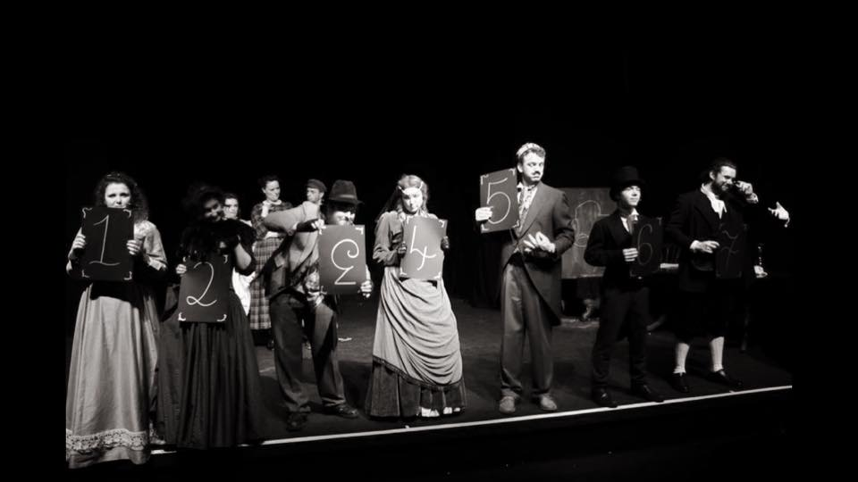 A scene from the Mad Props Theatre production of A Mystery of Edwin Drood. All of the cast are on stage and five of them are holding up numbers.