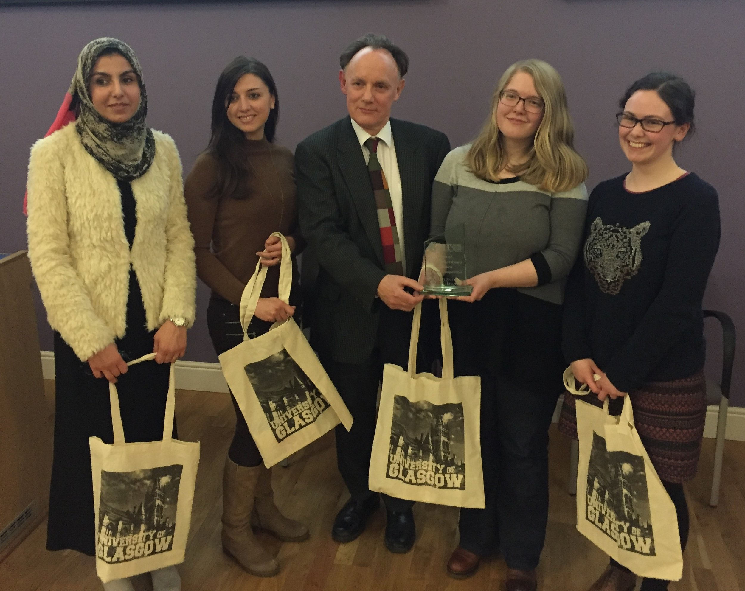 3MT Humanities contestants with their UofG branded bags and 2016 Humanities winner Ruth Turner holding her trophy