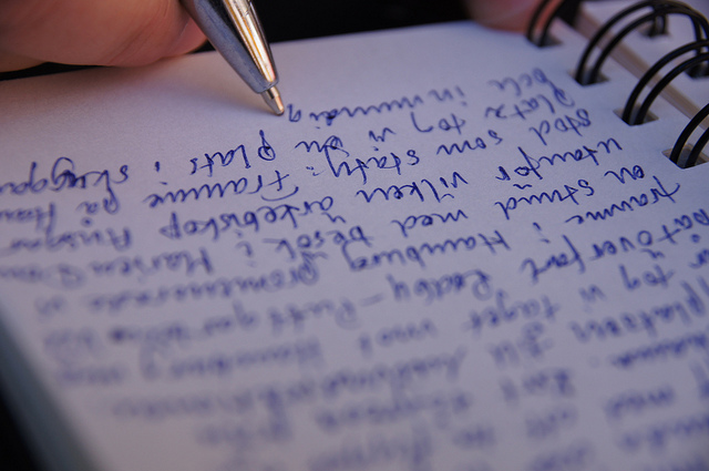 A hand writing with blue ink in a ring bound notebook