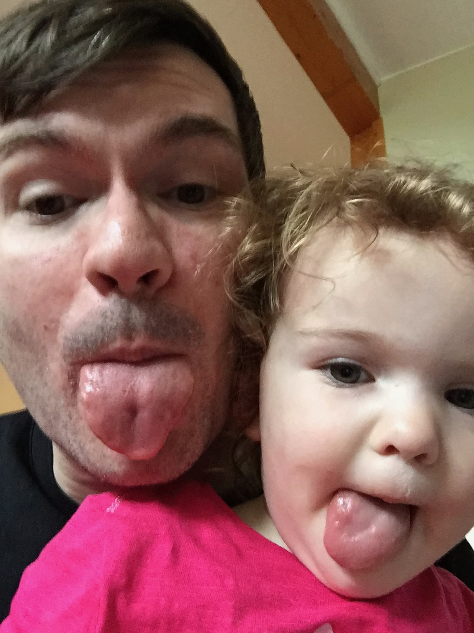 An image of a child and her father sticking out their tongues.