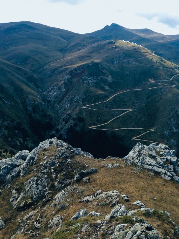 A mountain range with a road twisting through it.