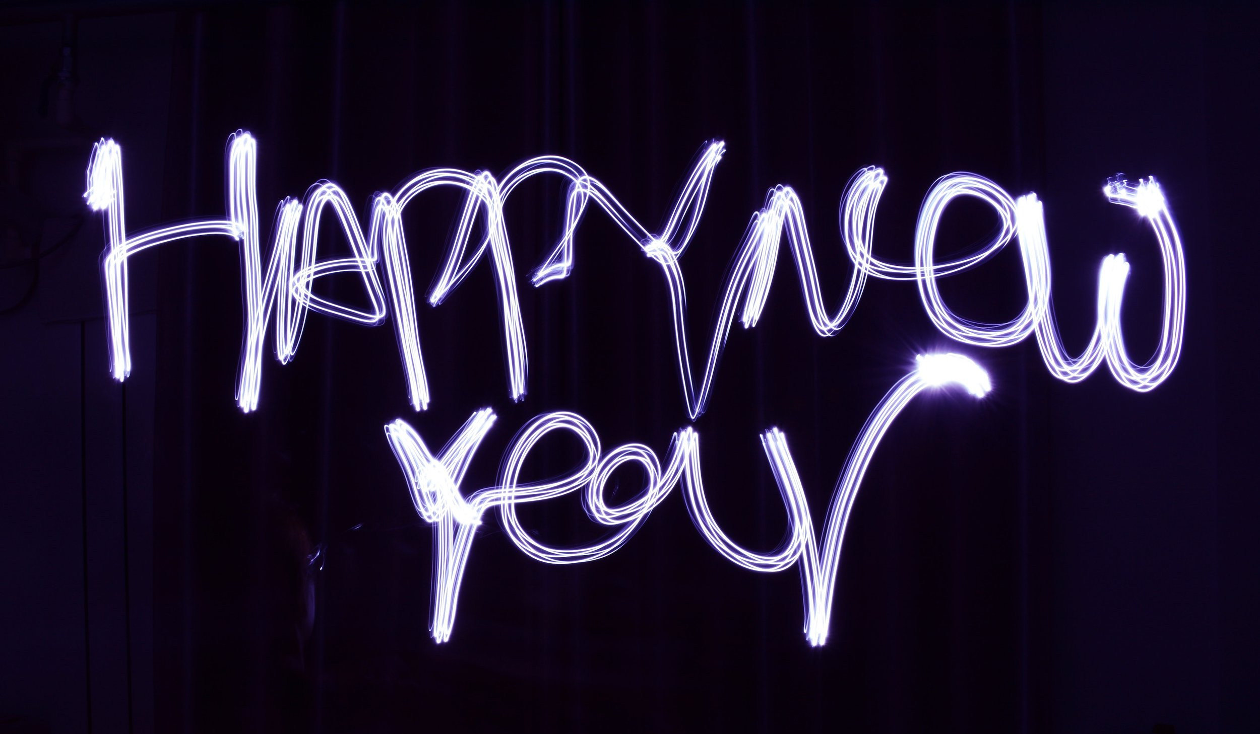 [Image description: 'Happy New Year' written in bright lights against a black background.]