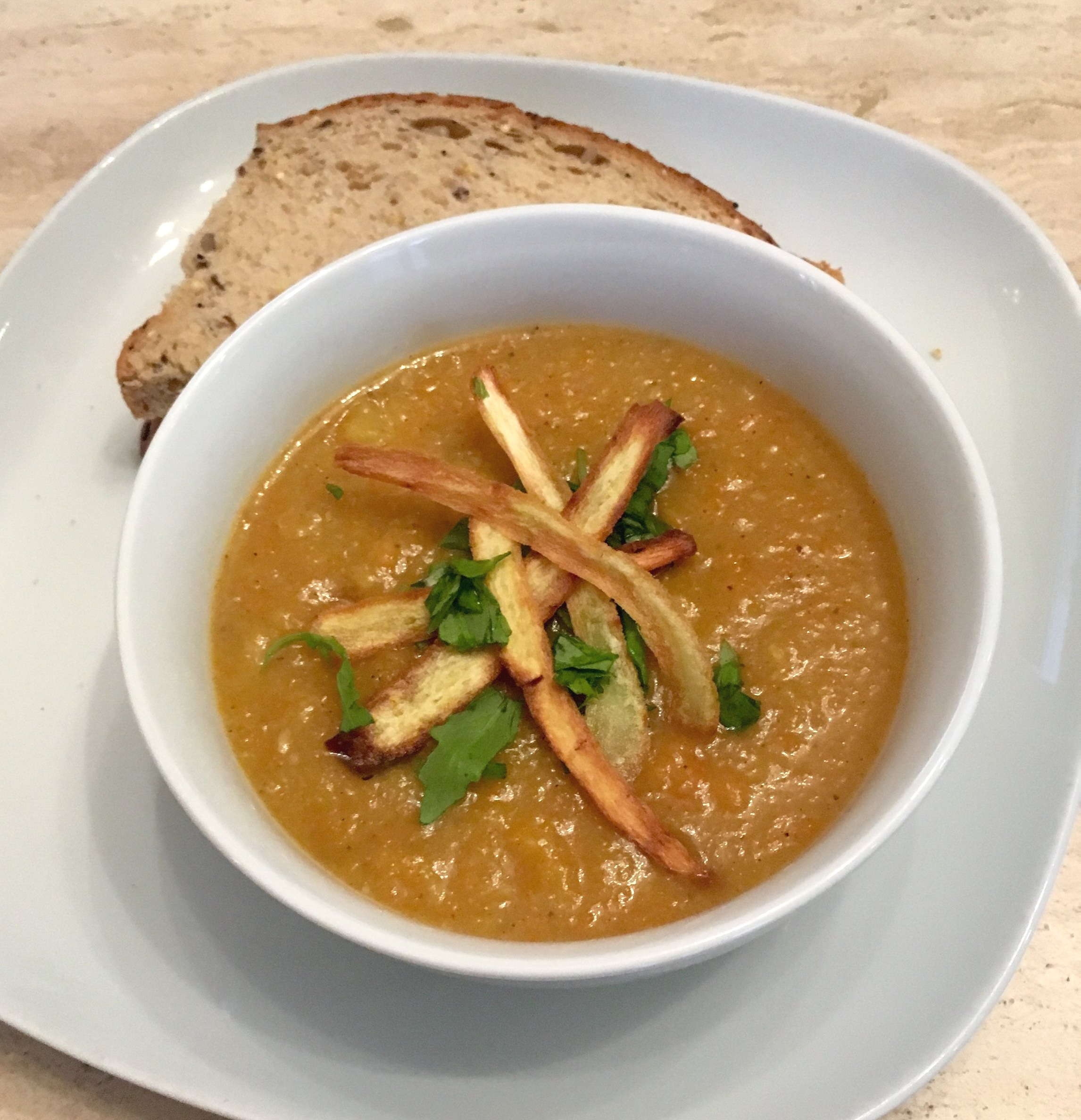 A bowl of carrot and parnsip soup with crispy parsnips and spinach on top. the Bowl is placed on top of a larger plate with 2 triangles of brown seeded bread.