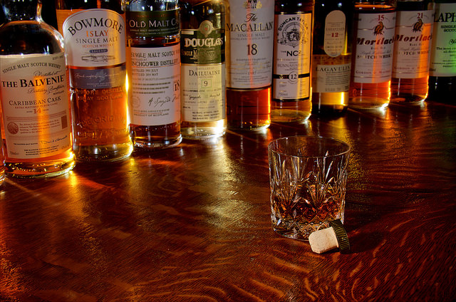 [Image Description: A vast selection of Whisky arranged in a half-circle around a dram of whisky, sitting on a wooden surface.]
