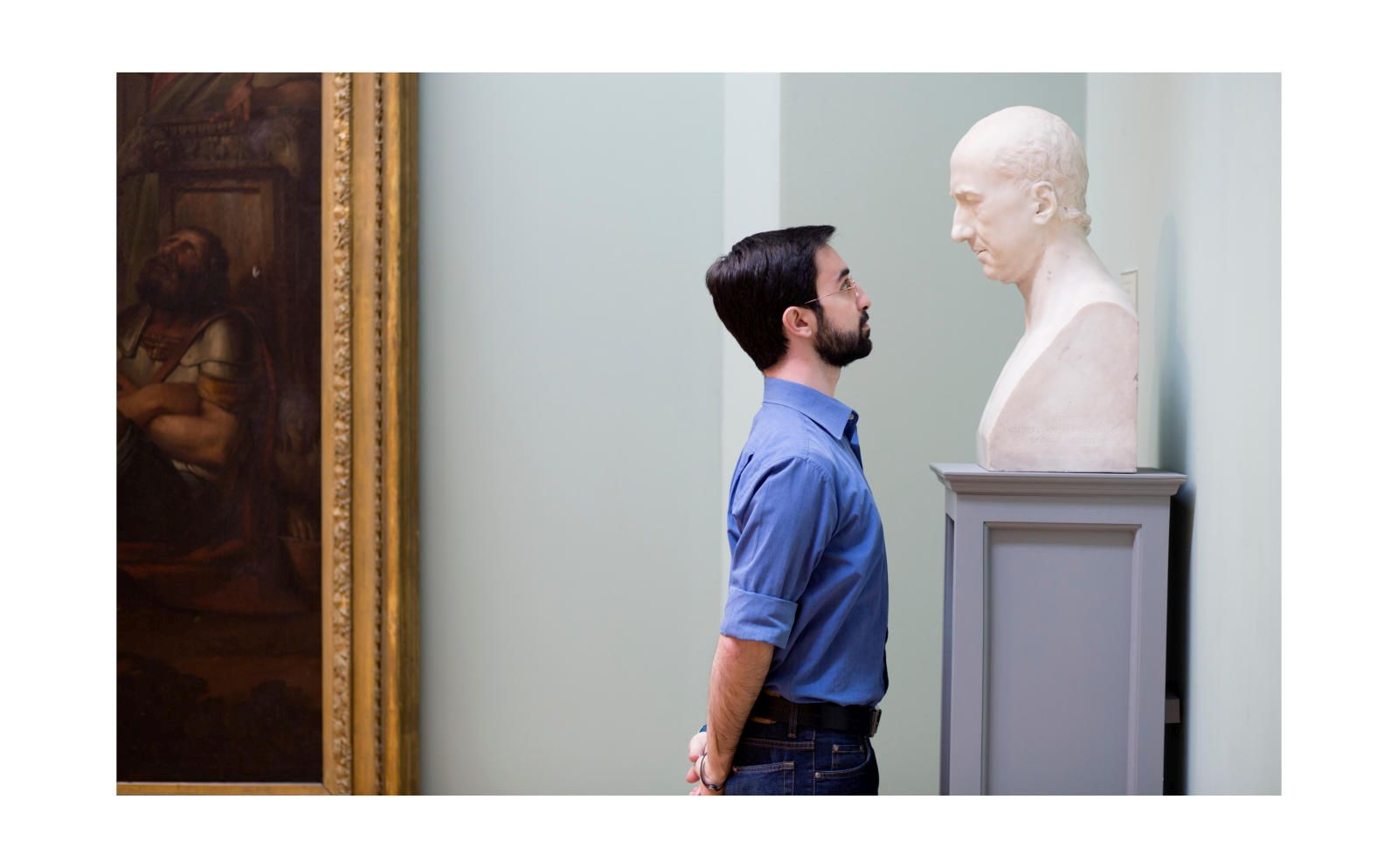 Man in a blue shirt staring eye to eye with a marble bust.