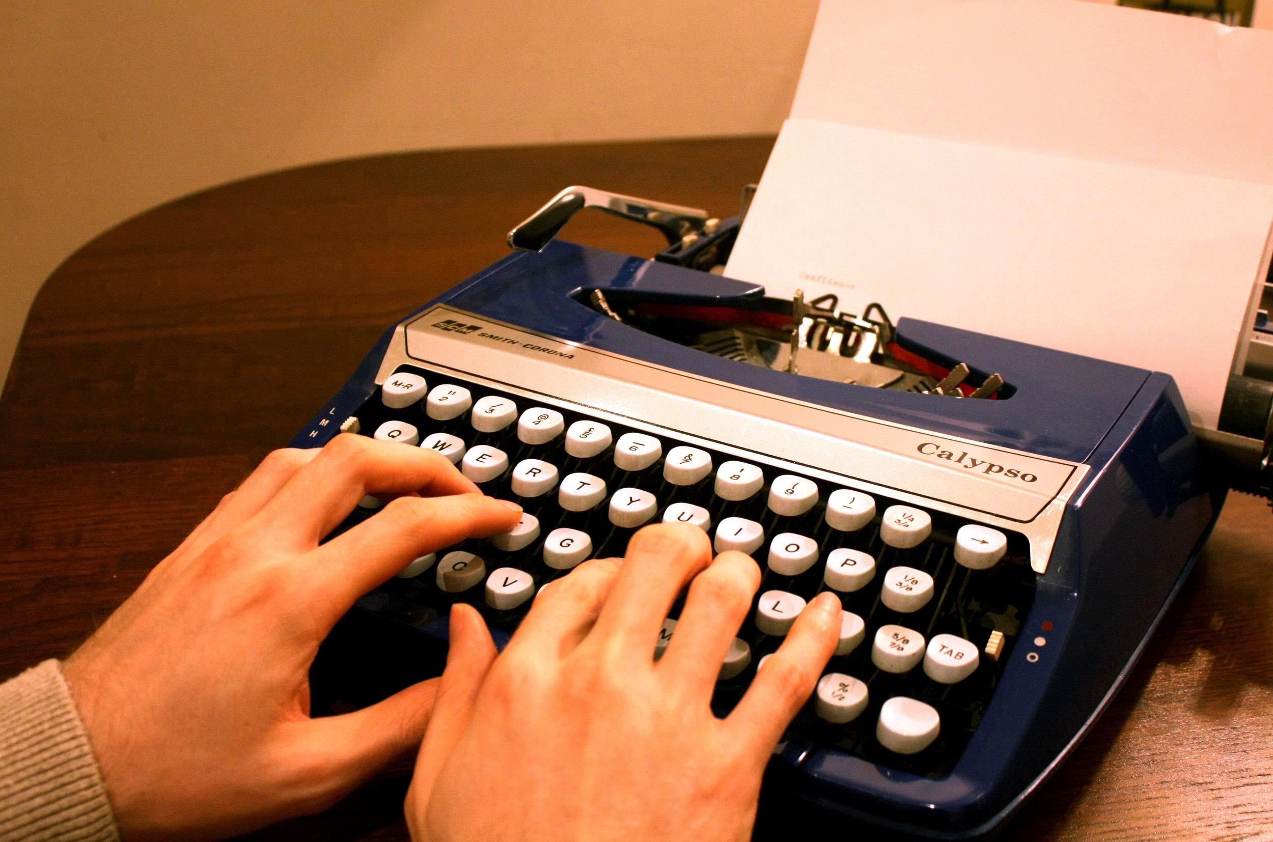 Hands on blue typewriter