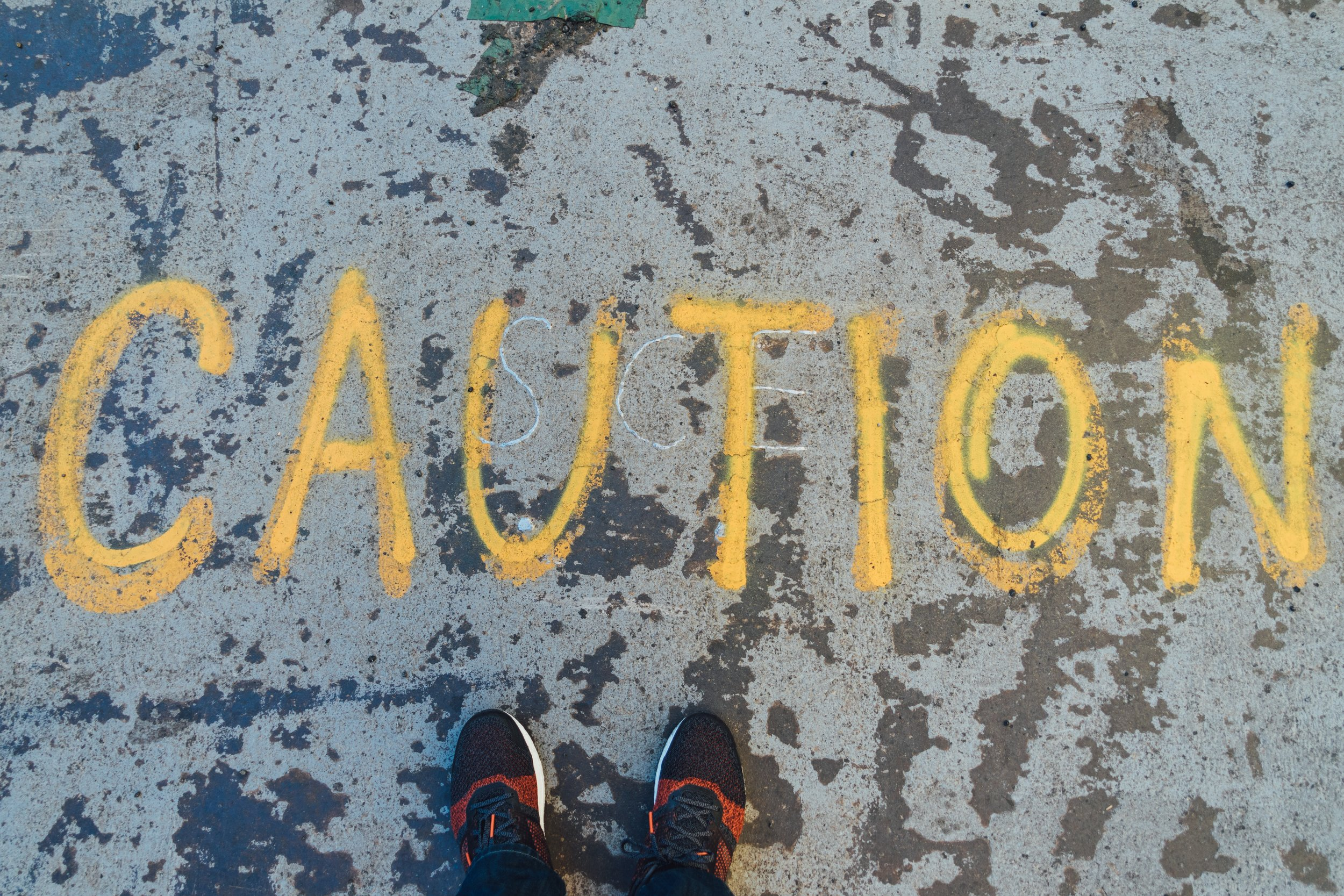 [Image description: The word 'Caution' is written on pavement in yellow chalk/paint and in all capital letters. A person stands just in front of it.]