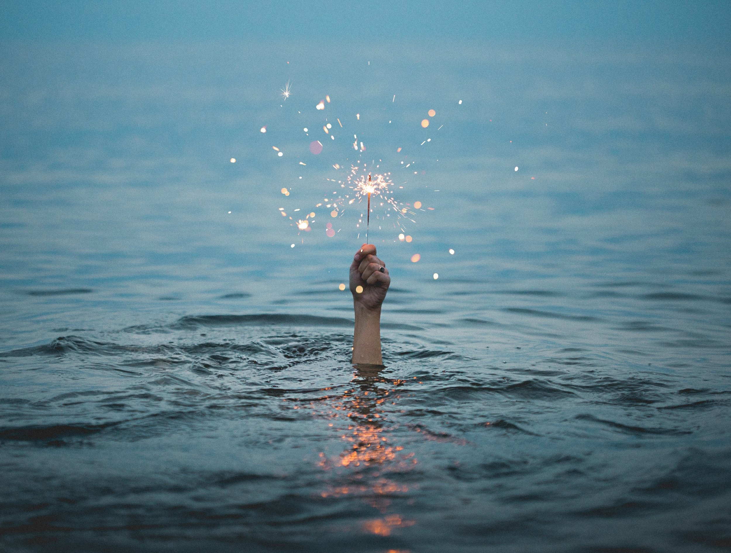 [Image description: An arm reaches from below a surface of water holding a lit sparkler.]