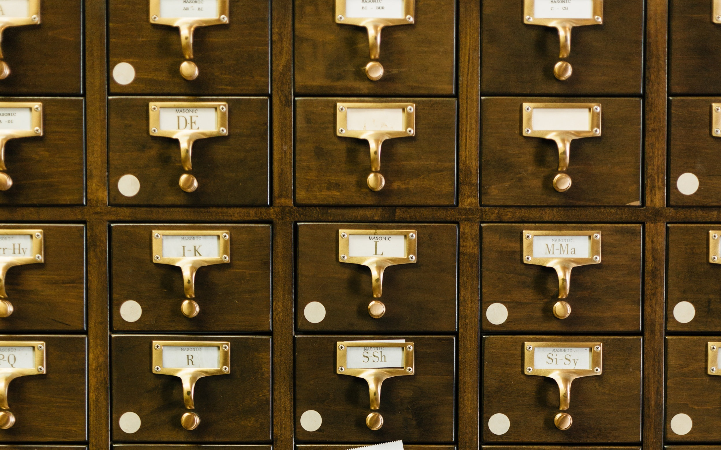 Old fashioned library filing system made of small wooden draws with brass alphabet labels