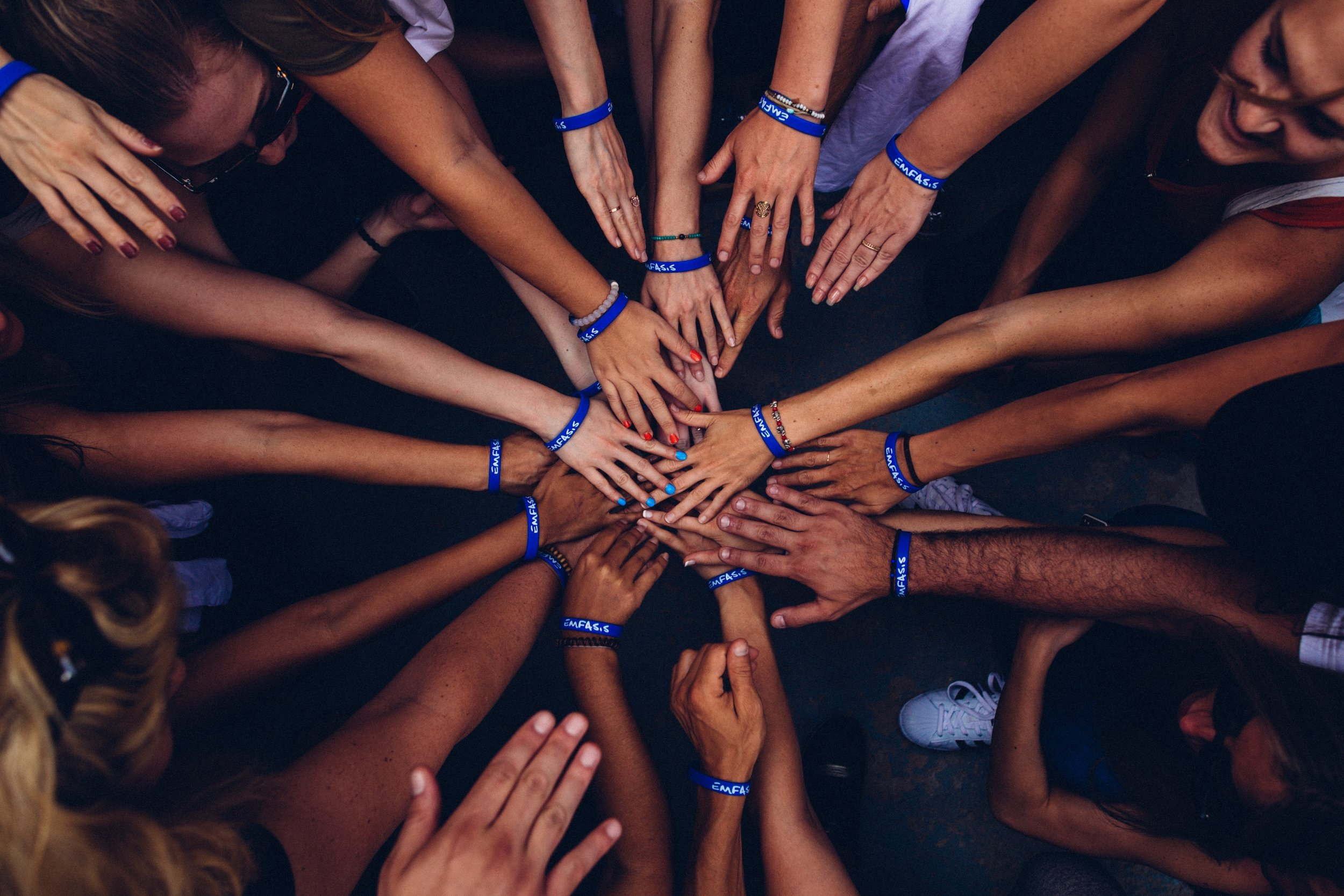 [Image Description: Several people put their hands together in the middle of a circle. The image looks down from above.]