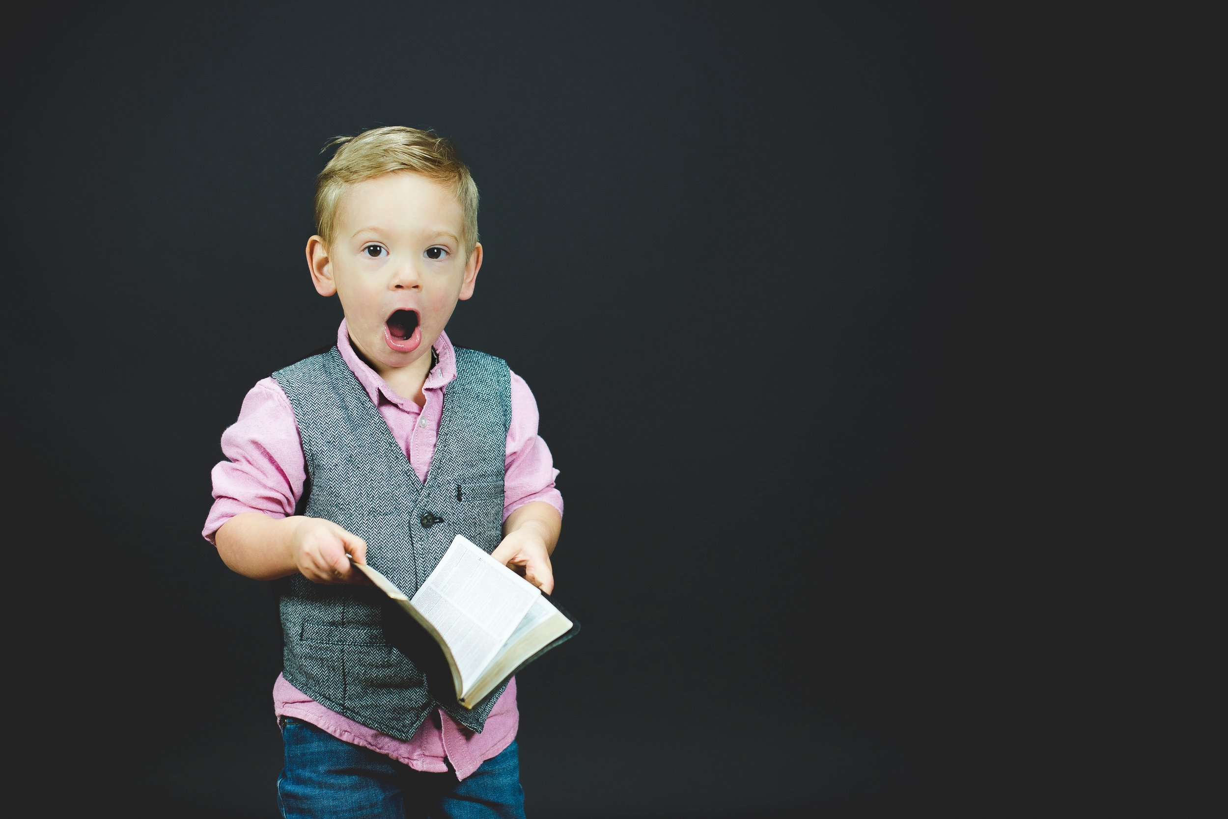 Boy looking shocked and holding an open book