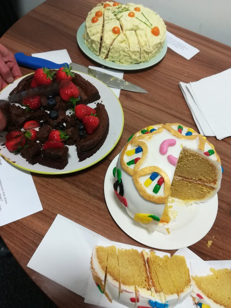 [Image Description: Three different cakes are shown on a table. One is round and contains decorations in the shapes of chromosomes; another is chocolate with strawberries and blueberries; and the last has different shapes connected to one another.]