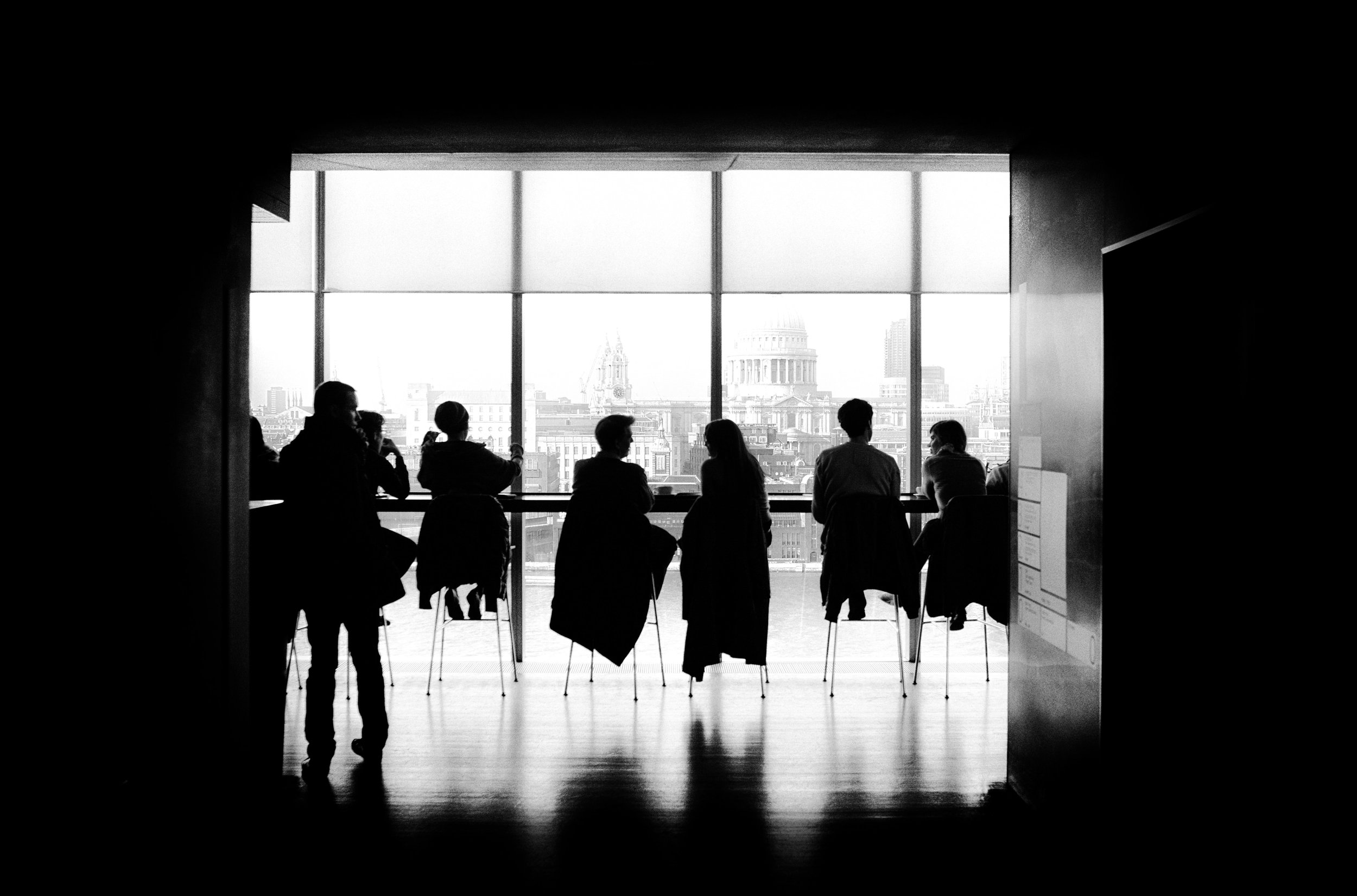 Black and white photo of people on chairs framed by a window.