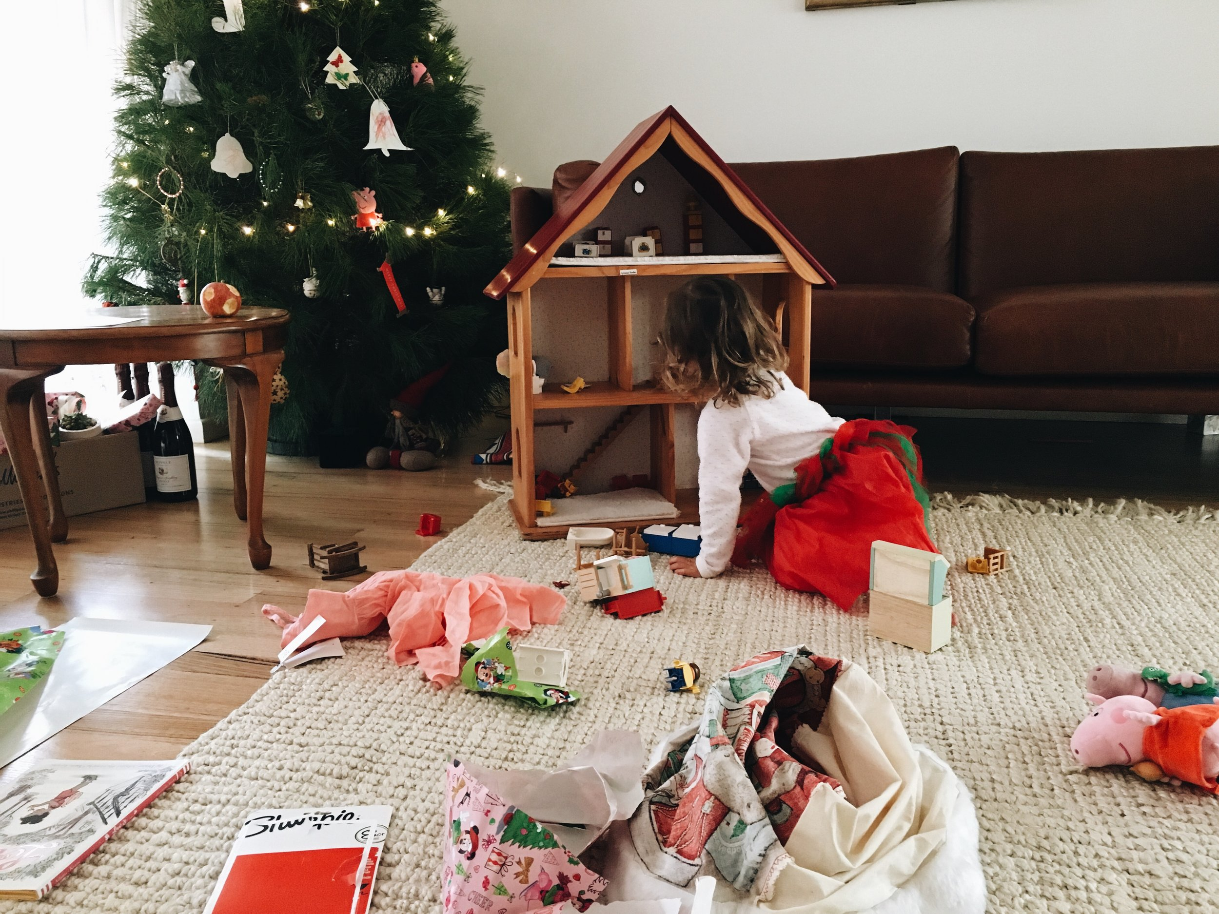 Wearing a tutu and playing with her new doll's house.