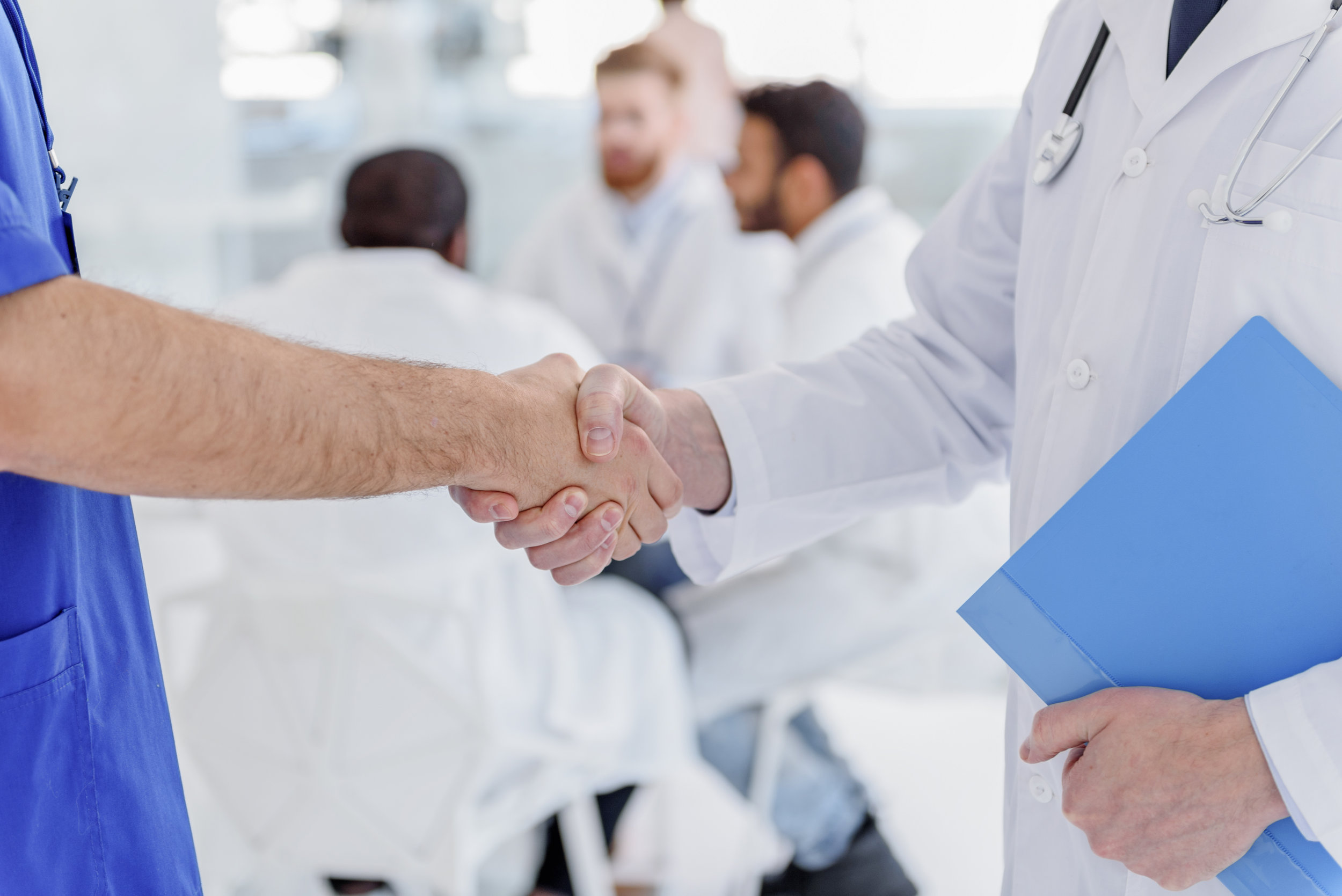 home - join -- stock-photo-medical-workers-greeting-each-other-by-handshake-568817293.jpg