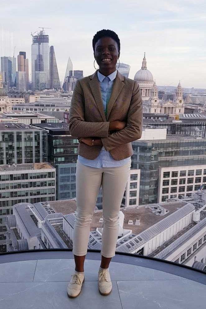 Nia in front of a skyline view of Central London from the Deloitte building for the Business Plan Competition Pitch Day