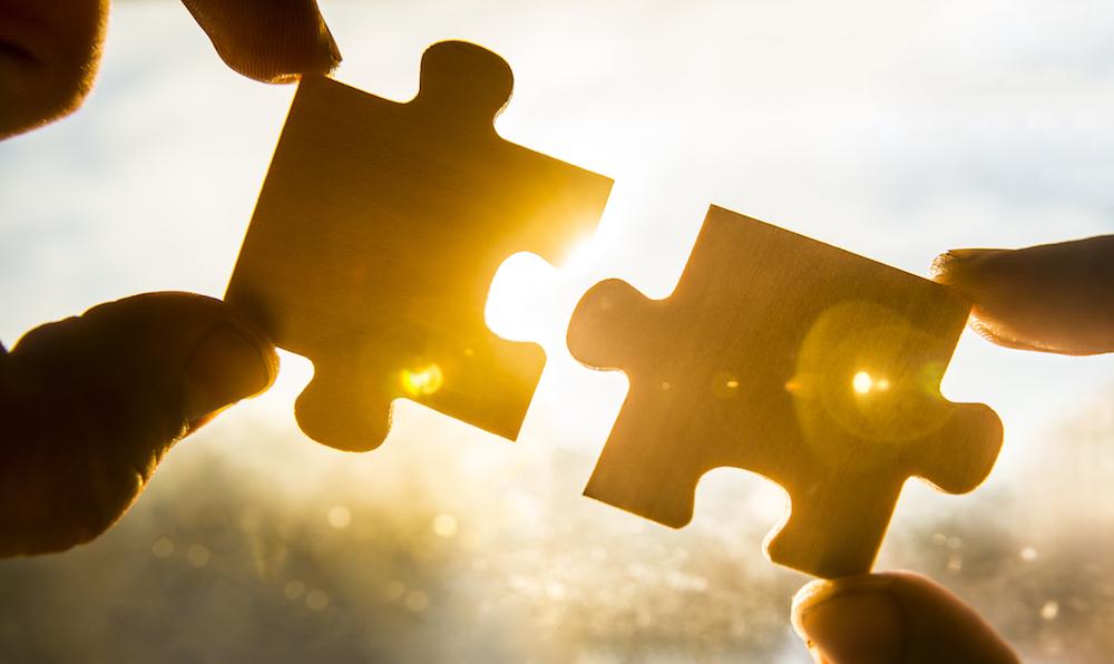 hands holding jigsaw pieces