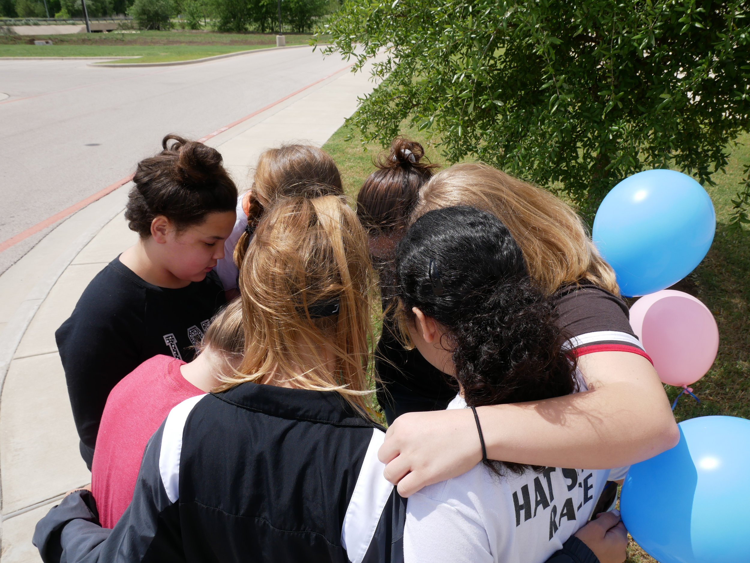 Girls praying together before releasing balloons.