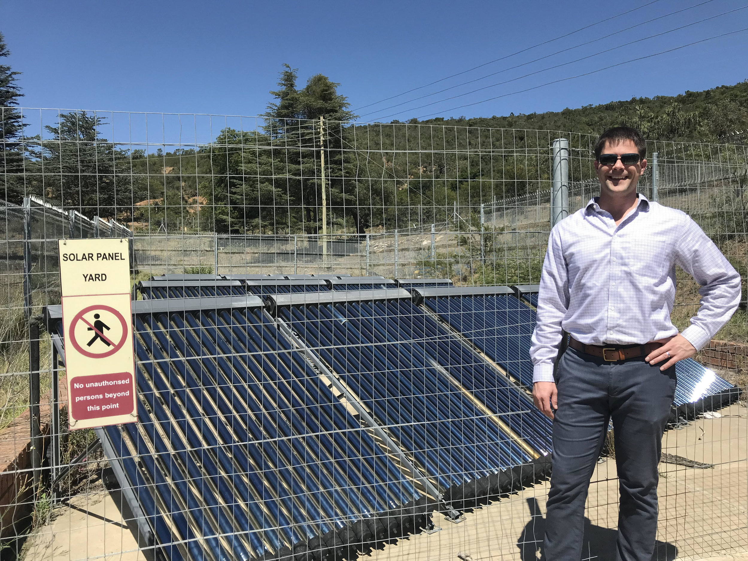 Optimus Solar President Ben Pauluhn in front of the solar panels that power the St. Matthews Girls Hostel water heating system.