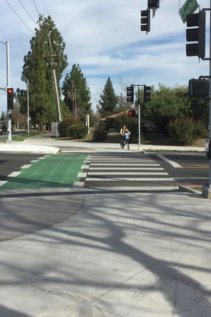 Bicyclist positioned in pedestrian area to push signal button to cross J Street