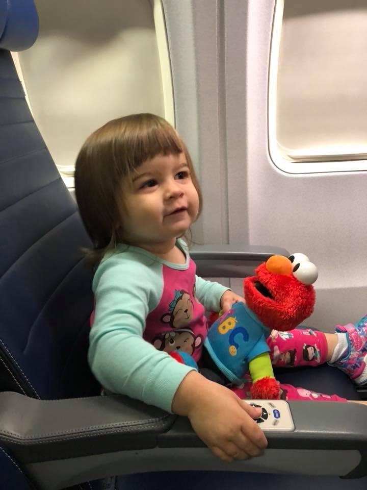 "Adaline and Elmo on the plane bound for Kansas to see ""Gram Gram."""