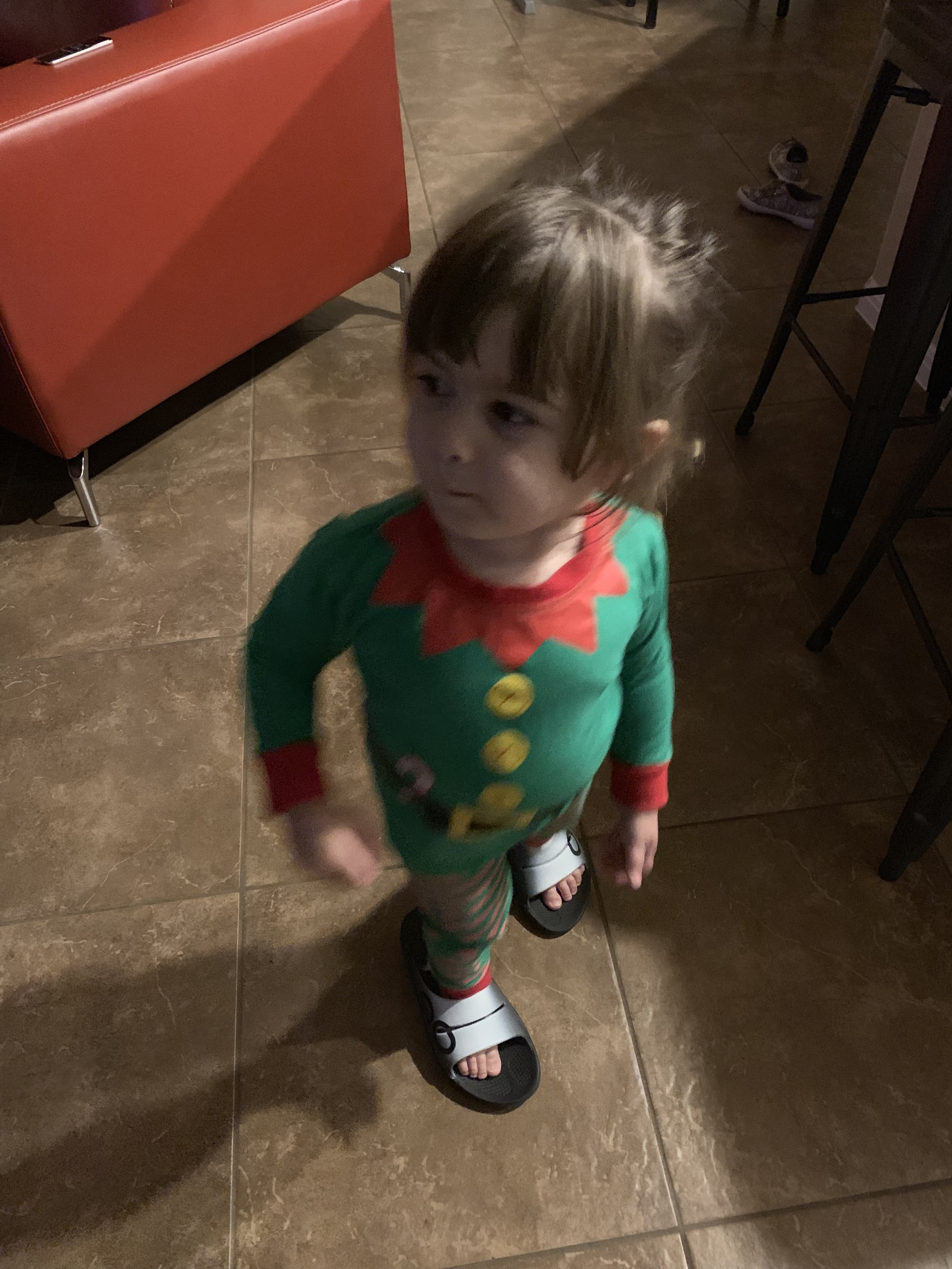 Ada in her elf jammies, wearing my sandals on her tiny feet.
