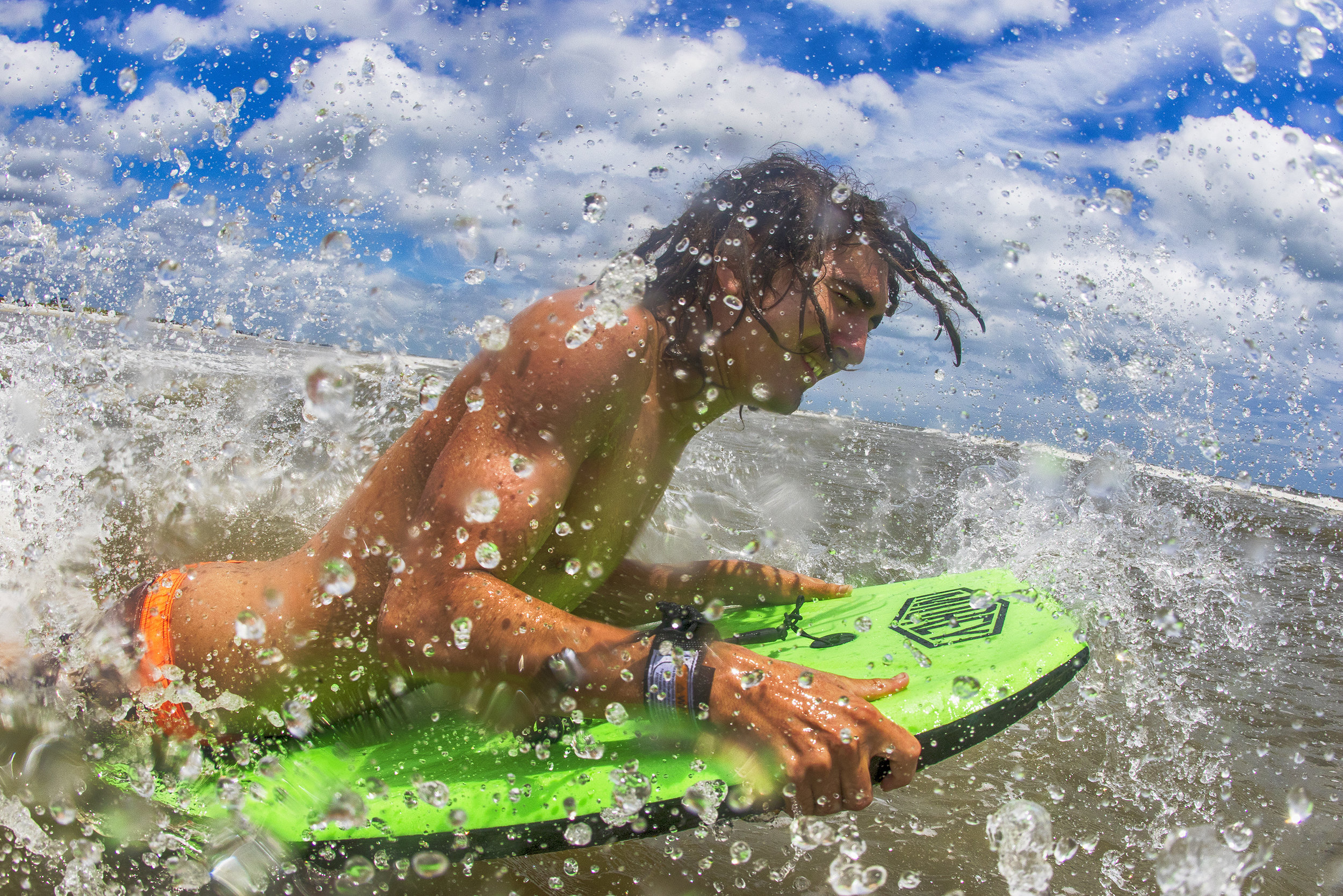 Blaze playing in the shorepound on the Boogie Board, dreadlocks and all.