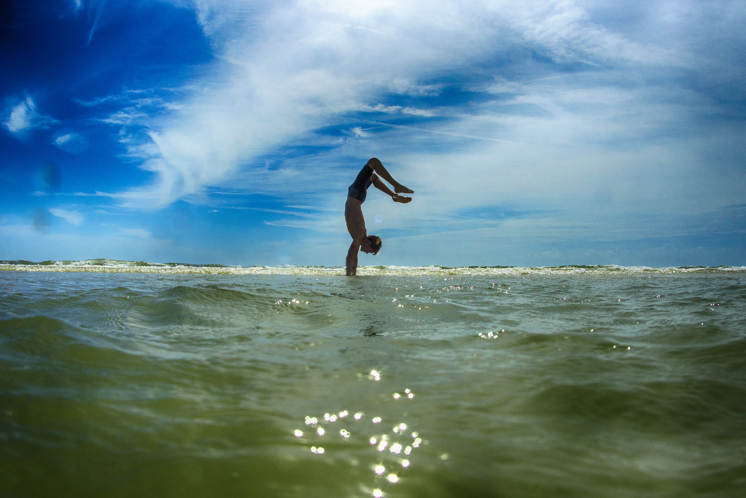 Zane hitting the hand stand in a shallow pool at New Smyrna Inlet.