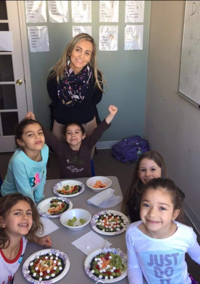 Alunos do programa Português Plus preparam comida como parte de sua aula sobre o Brasil.