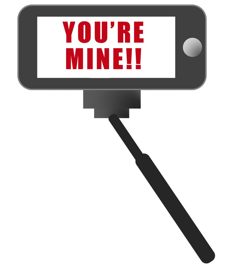 "Selfie stick and phone with ""You're mine!"" on the screen"