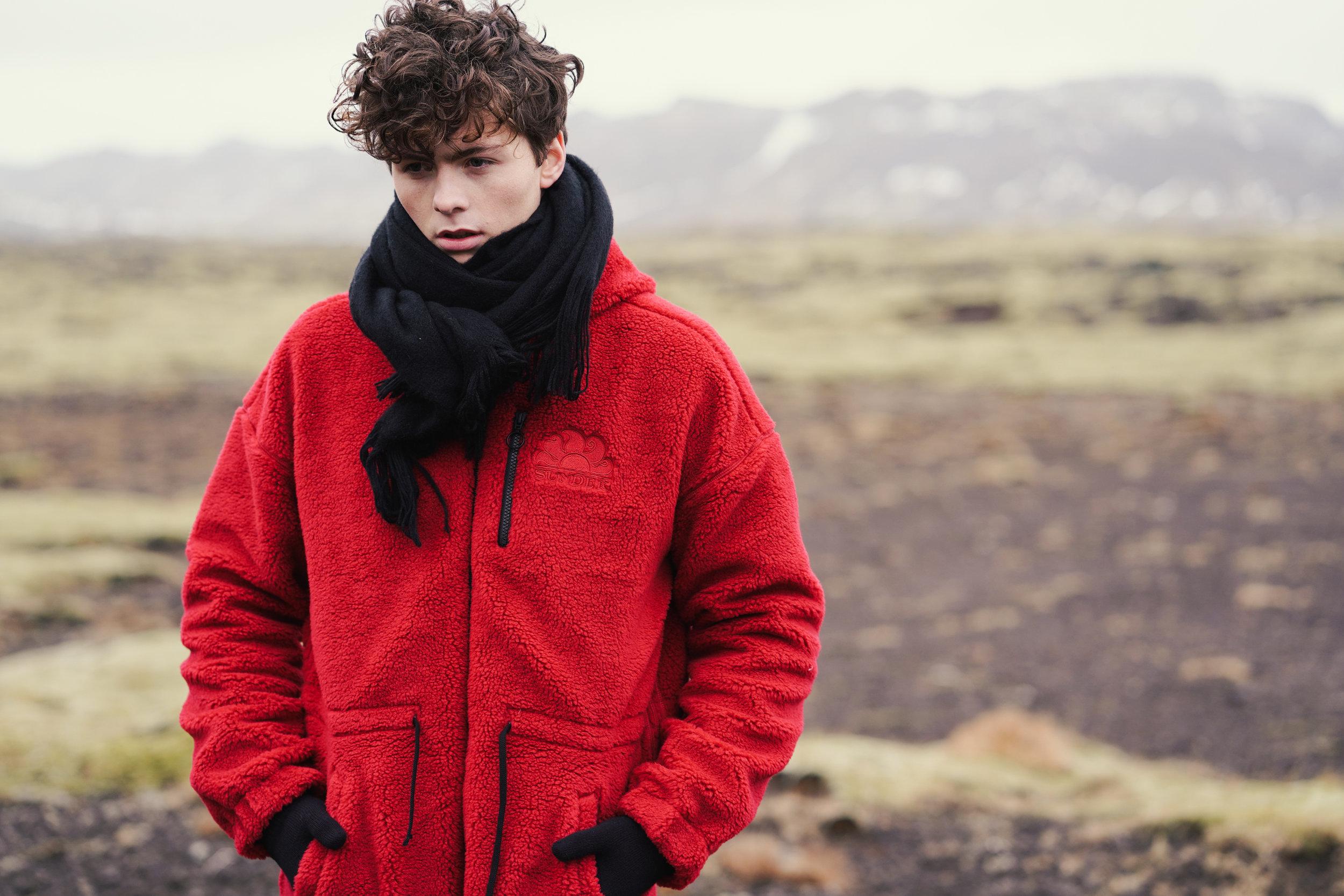 Sundek photoshoot Solon wearing red long jacket at Reykjarnes