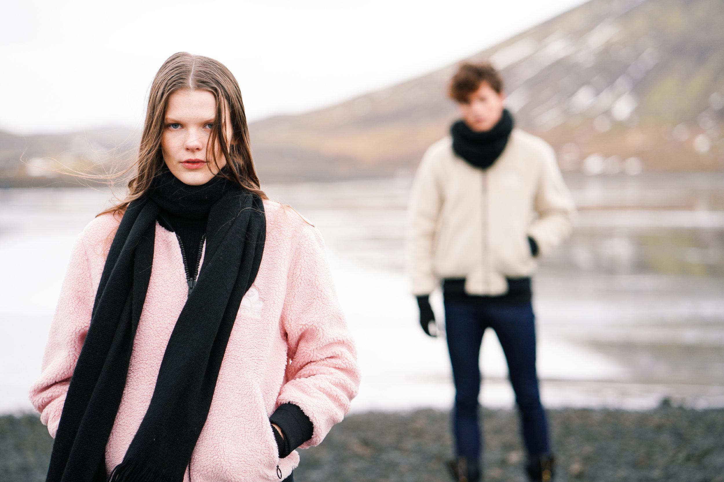 Sundek photoshoot Kristin wearing pink jacket and Solon in background wearing white jacket