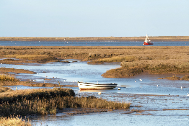 Boat in tidal muddy sea water marshes, Brancaster Staithe
