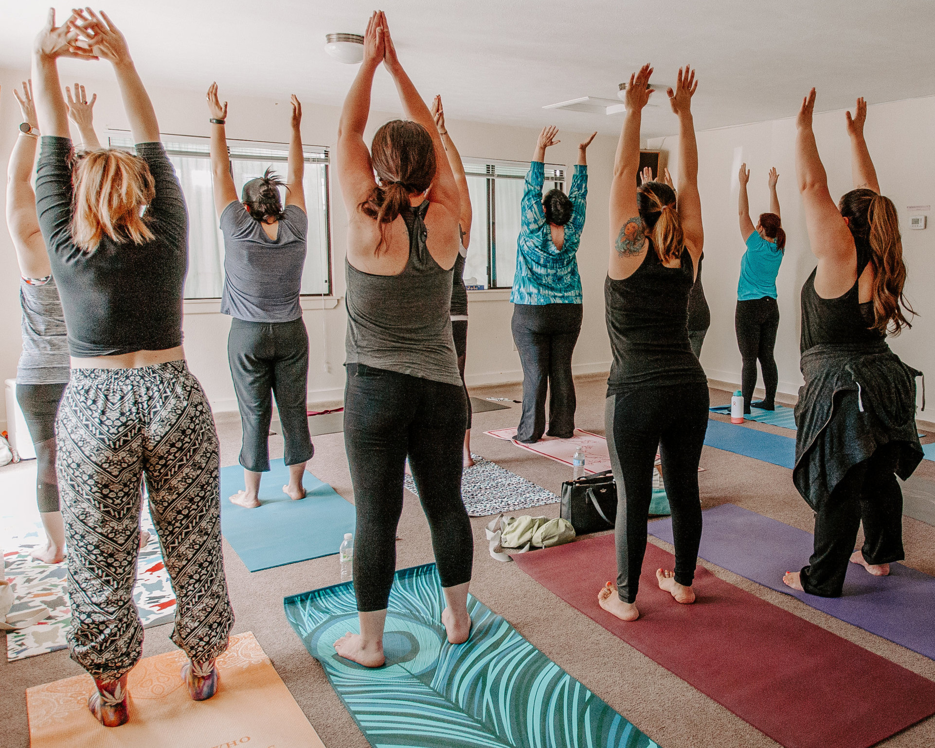 women stretching during light yoga by rast yogi at self-care event by kim baker beauty san jose california makeup artist photo by catie belle photography