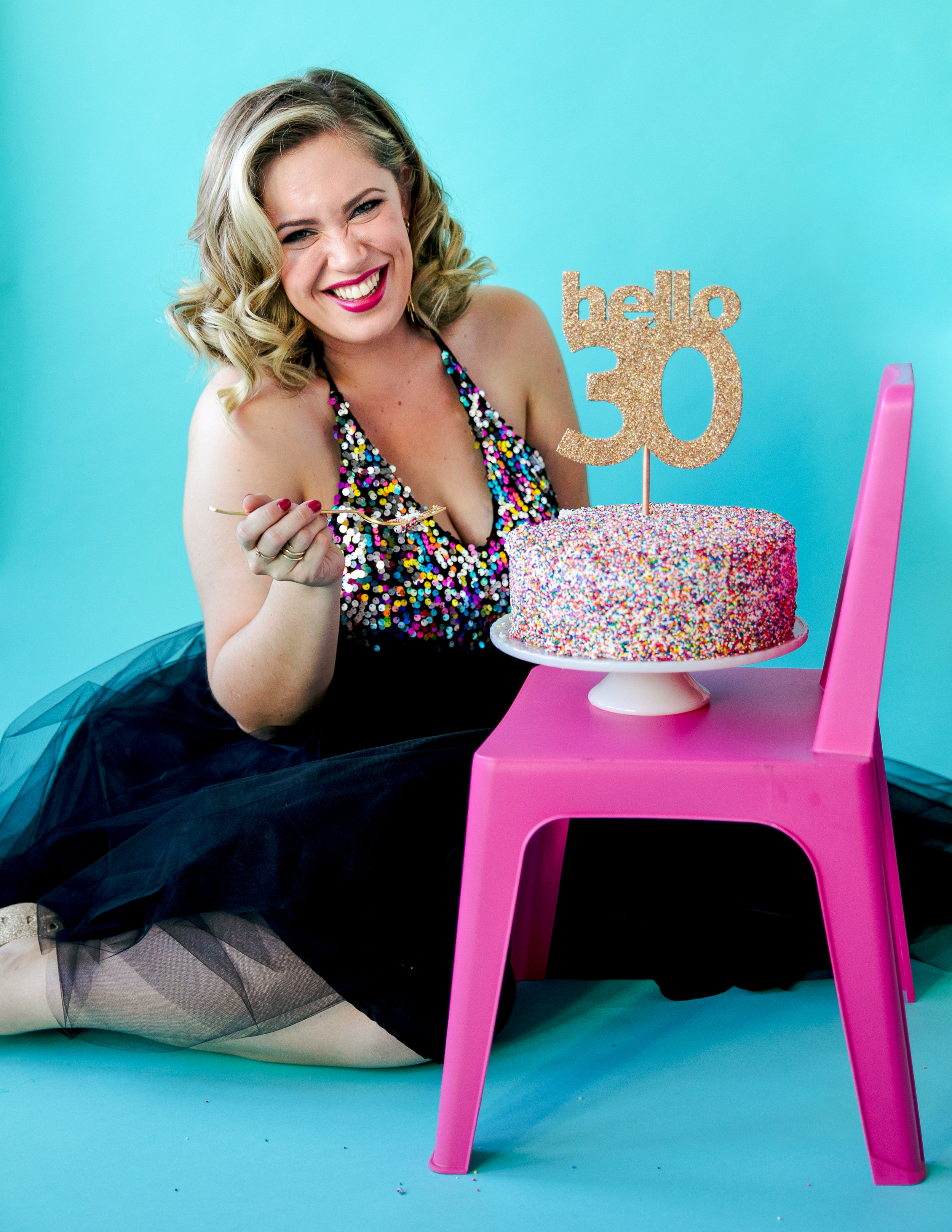 san jose california makeup artist kim baker beauty's milestone 30th birthday photoshoot with confetti cake and gold glitter cake topper teal background black tulle skirt and sequin rainbow top