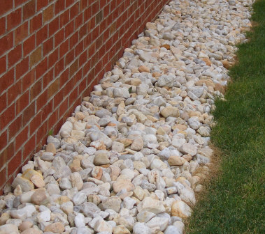 Shore stone - #2 to 4 Shore Stone along a brick wall. Rigid landscape edging could be added to contain the stone, create a more mowable /trimmable straight edge, and stop inward-growing lawn grasses. Purchase landscape edging