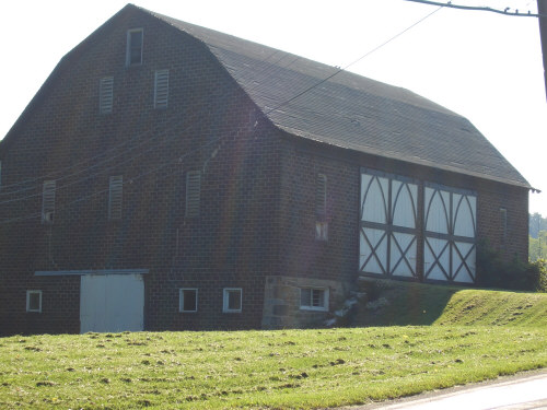 Large brown brick Barn with classic doors