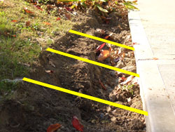 Use imaginary grade lines (yellow lines in the photo) to guide your soil grading work. Cut off the high spots enough to leave room for screened topsoil as your finish layer. -