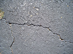 """Apply crack filler to any cracks over 1/8-inch wide. Cracks over 1/2-inch will require special work. Most crack fillers come in a one-gallon squeeze bottle -- trim the spout large enough to put down a nice size bead of crack filler. Look for buckets of """"trowel on"""" crack filler for larger cracks— NOTE: Some may require an extra day of dry time before you apply the finish sealer so plan ahead."""