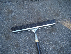 I prefer to use the brush side of the driveway applicator (shown facing up) for spreading the sealer. An 18-inch wide applicator works best on most driveways. It's easiest to work from the top of a slope toward the bottom (with gravity) and be sure not to paint yourself into any corners.