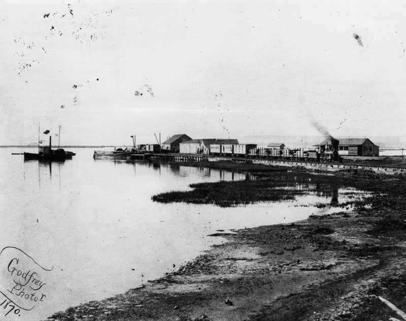 View of Wilmington harbor in 1870, showing the Los Angeles and San Pedro Railroad, which had been completed by Phineas Banning in 1869--the first railroad to the harbor. Before that, freight was transported to Los Angeles by ox carts and later by horse-drawn wagons.