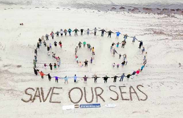 SOS KI: Participants at the Hands across the Sand protest action at Emu  Bay on Sunday spelled out Save our Seas with their bodies. Drone  photography by Greame Ricketts.