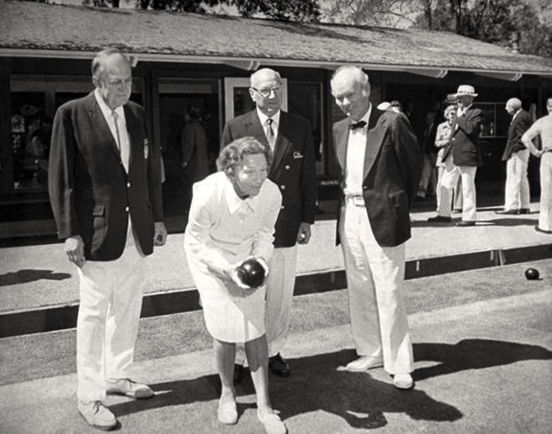 1974 Club president Paul Houseman (center), Monty Moncure (left), and Floyd Carpenter (right) look on as Gertrude Cobb prepares to bowl. The newly enlarged clubhouse is in the background. PAHA photo.